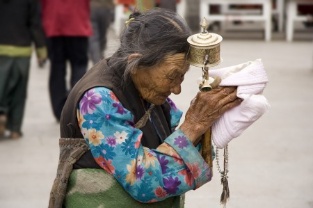 Elderly Tibetan Woman with Prayer Wheel and Recitation Beads