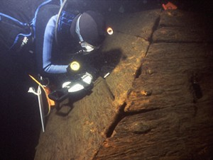 Underwater archaeologist Joseph W. Zarzynski makes a measurement of the starboard view hold on the 1758 Land Tortoise radeau shipwreck, a British warship from the French & Indian War.