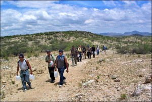 A group of immigrants attempting the trek across the US-Mexican border.  As you can see, they are carrying plastic jugs of water to stay hydrated, although the water likely is not enough.