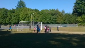 VAST Scholars play a game of soccer led by mentors Sarah and Roger.